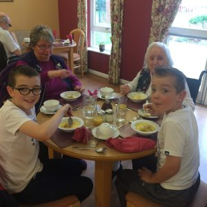 Children having lunch with the tenants at Aspen Gardens. Bridging the generational gap.