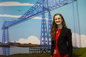 Local artist Abby Taylor standing in front of her graphic design of the Middlesbrough Transporter Bridge